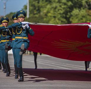 Военнослужащие несут флаг КР на площади Ала-Тоо в Бишкеке во время празднования 27-летия независимости Кыргызстана