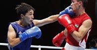 Кыргызстанец Азат Усеналиев (в синем) во время полуфинального боя с Ясурбеком Латиповым из Узбекистана на Азиатских играх в Джакарте. 31 августа 2018 года