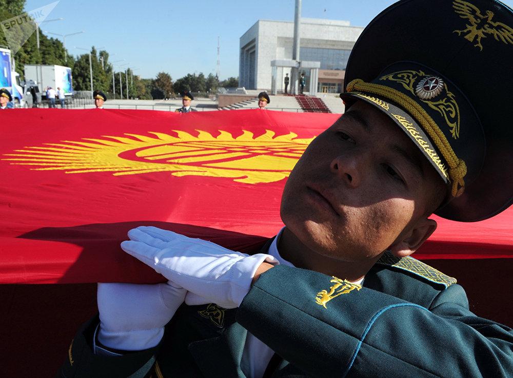 Улуттук гвардиянын жоокерлери эгемендүүлүктүн 27 жылдыгын майрамдоо маалында Ала-Тоо аянтында Кыргызстандын желегин көтөрүп баратат.