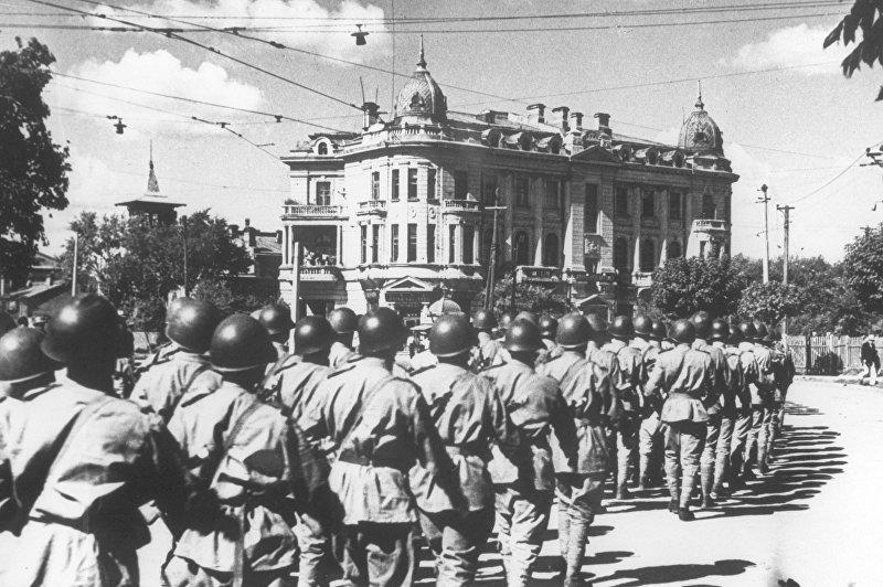 Советские войска проходят по одной из улиц Харбина (Северо-Восточный Китай). Разгром империалистической Японии в Маньчжурской операции. Вторая Мировая война (1939-1945). Снимок из фондов ЦГАКФД СССР.
