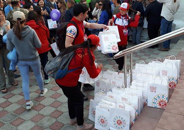 Волонтеры раздают пакеты с подарками пришедшим на церемонию открытия III Всемирных игр кочевников в ипподроме Чолпон-Аты