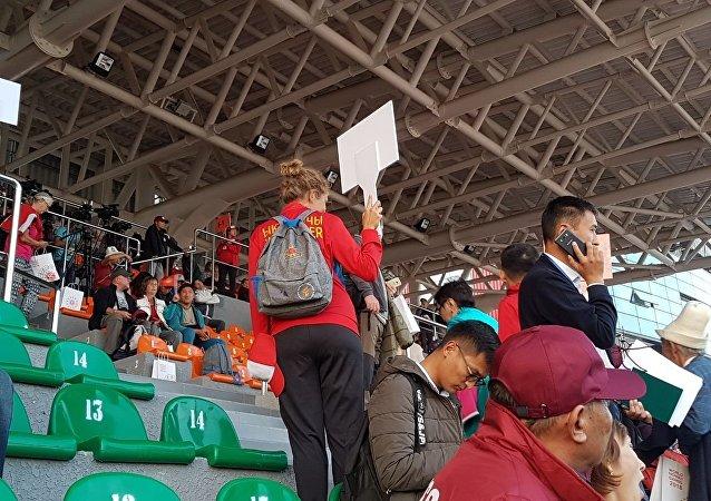 Зрители и волонтеры на трибуне ипподрома в Чолпон-Ате перед церемонией открытия III Всемирных игр кочевников