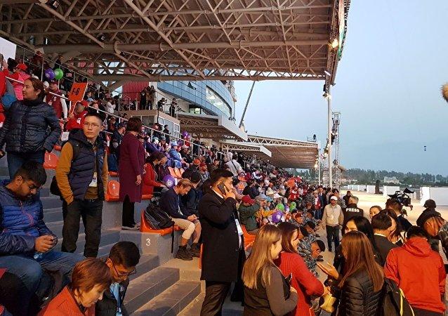 Зрители на трибуне ипподрома в Чолпон-Ате перед церемонией открытия III Всемирных игр кочевников