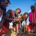 Кениядагы Масаи Мара айылында масаи уруусундагы эркек от тутандырууда.