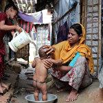 Рохинджа уруусундагы аял Бангладештеги качкындар лагеринде баласын жуунтууда.