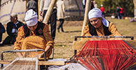 Женщины пряжут нитки в национальных костюмах на открытии этногородка Кыргыз айылы в ущелье Кырчын Иссык-Кульской области в рамках III Международных игр кочевников. Архивное фото