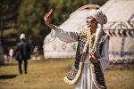 Девушка в национальной одежде делает селфи. Архивное фото