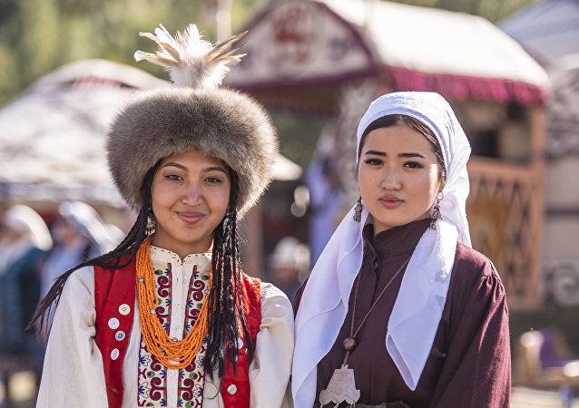 Девушки в национальном костюме у юрты в этногородке Кырчын на третьих всемирных играх кочевников