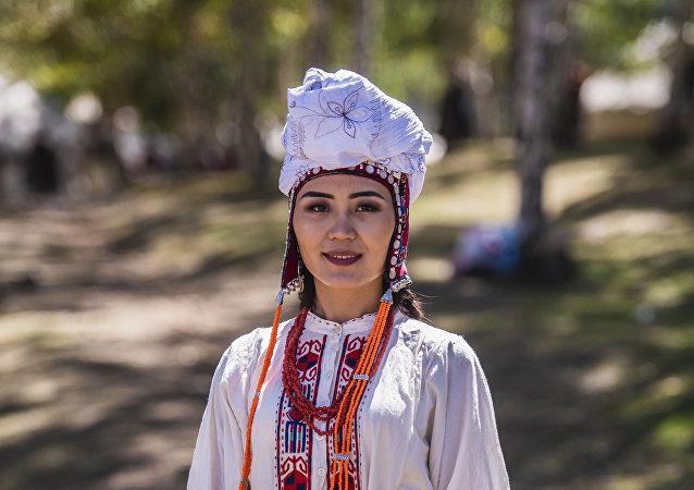Девушка в национальном костюме у юрты в этногородке Кырчын на третьих всемирных играх кочевников
