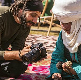 Турист показывает на фотоаппарате снимок женщине в национальной одежде. Архивное фото