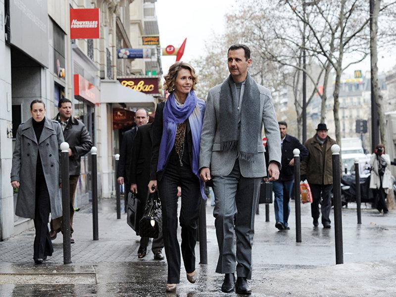 Сирийский президент Башар аль-Асад и его жена Асма выходят на улицу в Париже. Аль-Асад находится с двухдневным официальным визитом во Францию. 10 декабря 2010 года