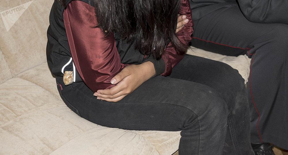 Девочка сидит на диване рядом с сотрудником милиции. Архивное фото