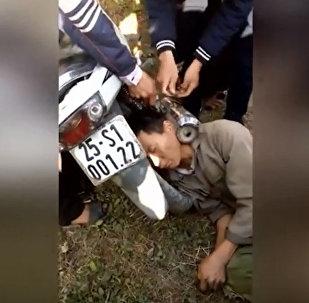 Вьетнамец засунул голову между выхлопной трубой и колесом мотоцикла — видео