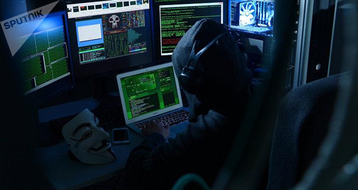 Мужчина имитирует взлом компьютера. Архивное фото