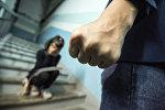Кулак мужчины на фоне девочки в подъезде. Иллюстративное фото