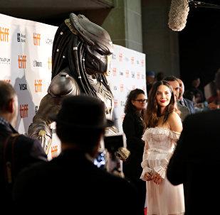 Аамериканская актриса Оливия Манн рядом с костюмом хищника на премьере фильма режиссера Шейна Блэка Хищник в Торонто. 7 сентября 2018 года