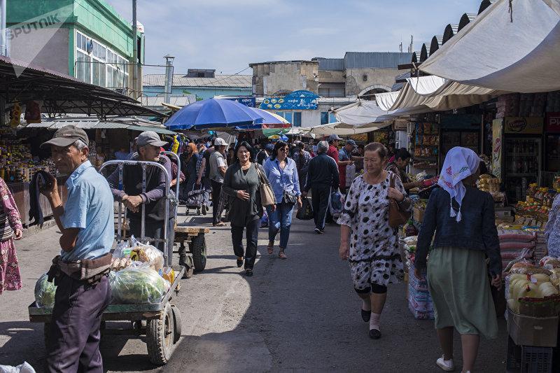 Люди идут по центральному ряду Ошского рынка в Бишкеке