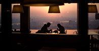 Пара в ресторане с видом на горизонт. Архивное фото