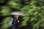 Девушка с зонтом идет по улице во время сильного дождя. Архивное фото