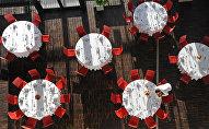 Официант сервирует столы на мероприятии. Архивное фото