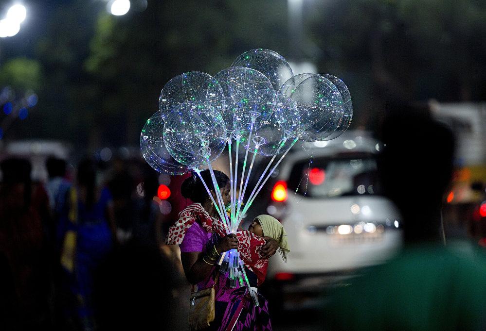 Индиянын Хайдарабад шаарында аял бир колуна баласын көтөрүп алып аба шарларын сатып жүрөт.