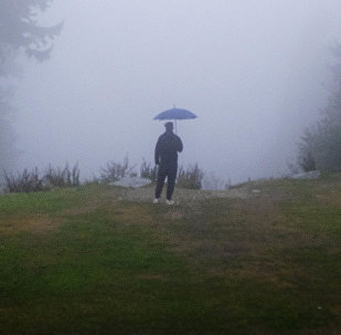 Человек с зонтом в горах. Архивное фото