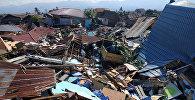 Люди разбирают завалы после землетрясение в индонезийском городе Палу. 30 сентября 2018 года