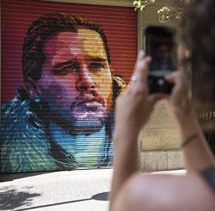 Женщина снимает на мобильный телефон с граффити уличного художника, изображающего британского актера Кита Харингтона, известного в сериале Игра престолов как Джон Сноу. Архивное фото