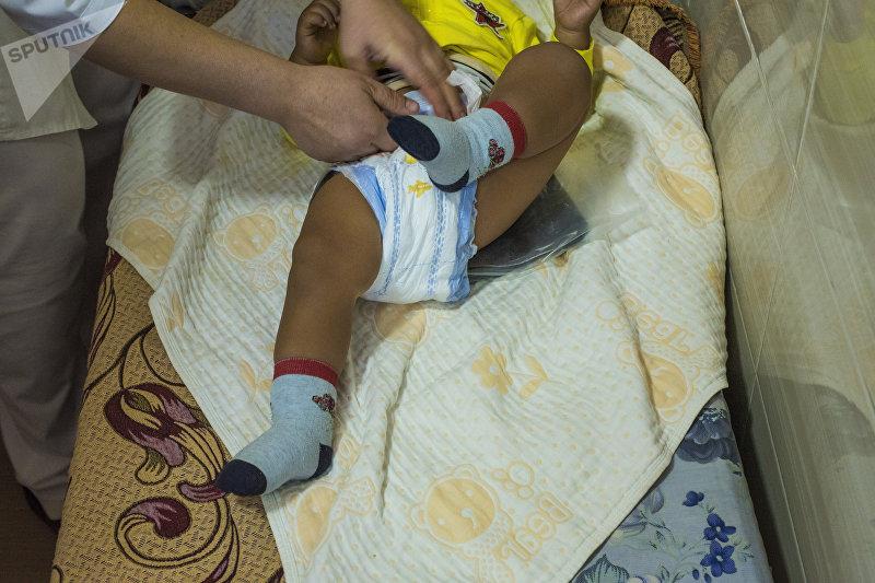 Ребенок на процедуре парафинотерапии в национальном центре охраны материнства и детства в Бишкеке