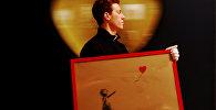 Сотрудник гуляет с картиной художника Бэнкси Девушка и воздушный шар в аукционном доме Bonhams в Лондоне