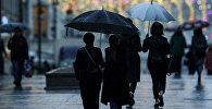Прохожие на одной из улиц во время дождя. Архивное фото