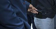 Ууру телефонду чөнтөктөн чыгарууда. Иллюстративдик сүрөт