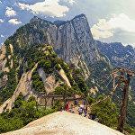 Гора Хуашань, Китай. Туристам предлагают пройтись по доскам, прибитым к скале. Не упасть с огромной высоты помогает страховка. Это особый аттракцион для любителей экстрима. Надо заплатить 30 юаней за специальное страховочное снаряжение, надеть его и прицепиться к железной цепи, намертво закрепленной в скале над тропой. Двигаться следует медленно и осторожно, так как тропа не имеет никаких ограждений, она просто висит над пропастью. Люди идут в обе стороны, и разойтись на узкой деревянной дороге очень непросто. Главные недостатки этой тропы — обилие туристов и периодически наплывающий туман. Смельчаки уверяют, что это совсем не страшный и безопасный аттракцион.
