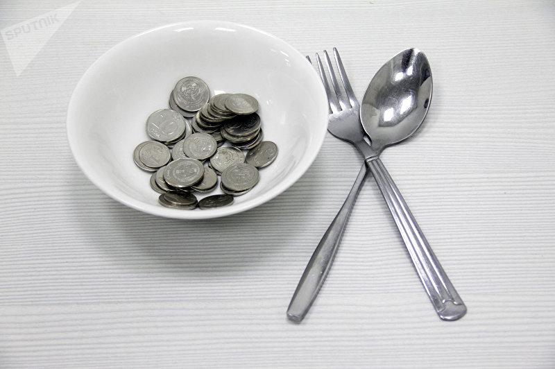 Национальные монеты в тарелке и ложка с вилкой. Архивное фото