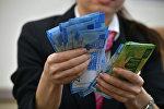 Сотрудница банка пересчитывает денежные банкноты рублей. Архивное фото