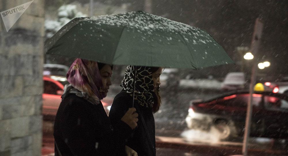 Девушки с зонтом во время снега с дождем. Архивное фото