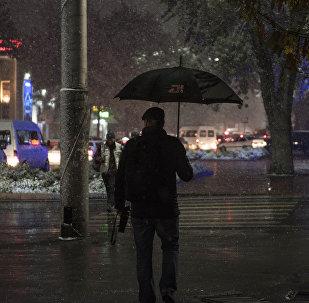 Мужчина с зонтом во время осадков. Архивное фото