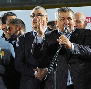 Заслуженный тренер России Абдулманап Нурмагомедов (справа) выступает во время встречи его сына бойца смешанного стиля Хабиба Нурмагомедова (слева) с болельщиками на стадионе. Архивное фото