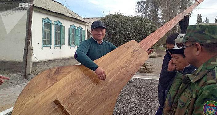 Комуз Абдрахманов көчөсүндө жайгашкан. Анын узундугу — 4 метр, туурасы — 1 метр, кылынын узундугу — 3 метр 80 сантиметр.