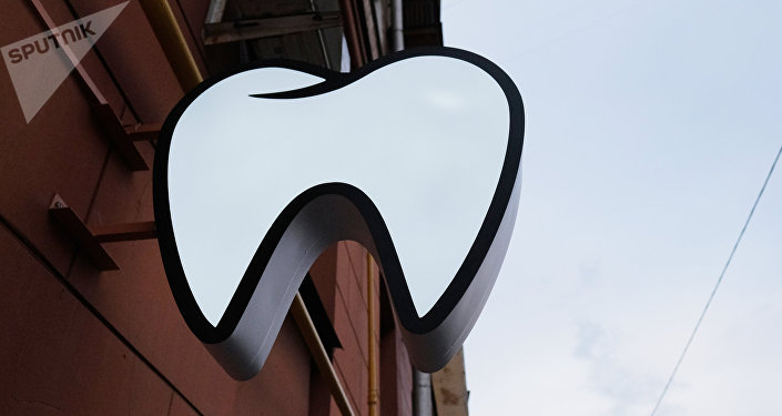 Вывеска в форме зуба надо входом в стоматологический кабинет. Архивное фото