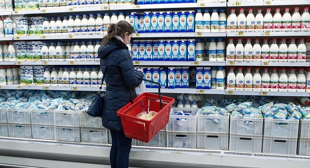 Покупатель у прилавка с молочной продукцией в магазине. Архивное фото