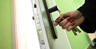 Женщина закрывает дверь квартиры. Архивное фото