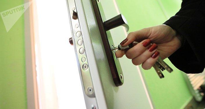 Женщина открывает дверь квартиры. Архивное фото