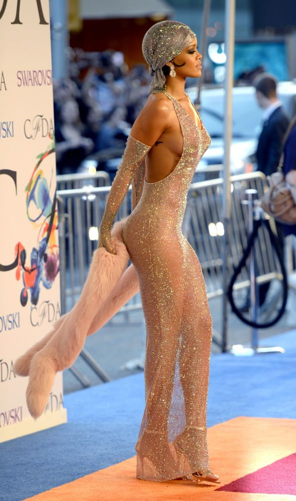 Любительница эпатажных и сексуальных образов Рианна пришла на одну из церемоний вручения премии Fashion Awards в очень тонком просвечивающем платье, после чего ее назвали иконой стиля. Платье от Adam Selman было сделано на заказ из серебристой ткани-сетки, на которую вручную нашили 230 тысяч стразов и кристаллов Swarovski.