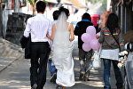 Молодожены прогуливаются по улице для фотосессии. Архивное фото