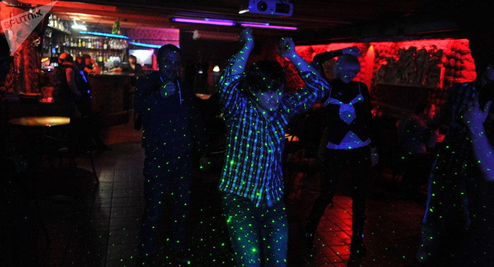 Молодые люди танцуют на дискотеке в одном из ночных клубов. Архивное фото