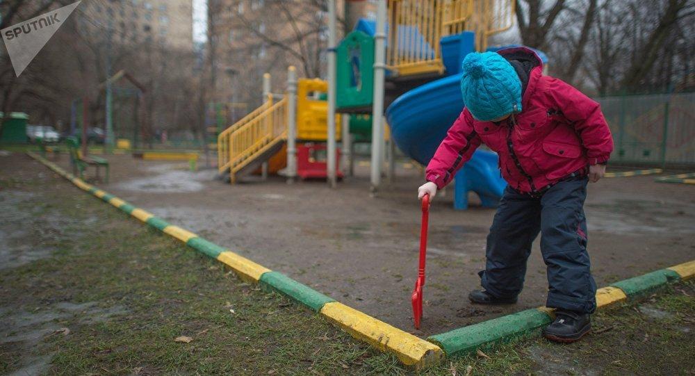 Девочка играет на детской площадке во дворе дома. Архивное фото