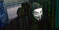 Человек в маске имитирует хакерскую деятельность. Архивное фото