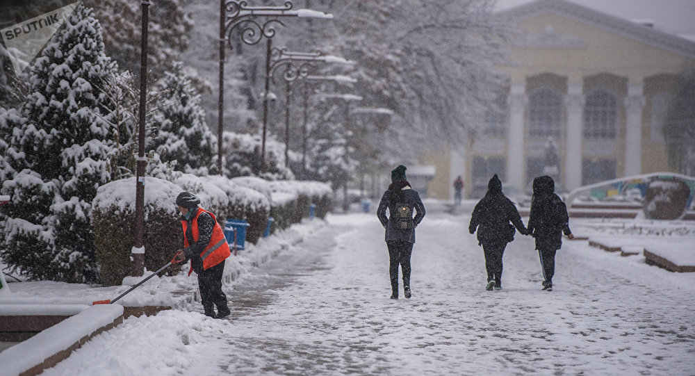 Сотрудница МП Тазалык убирает снег во время непогоды в Бишкеке. Архивное фото