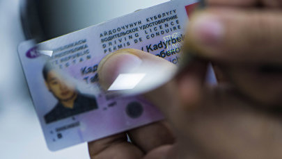 Мужчина держит лупу с водительским удостоверением КР. Архивное фото